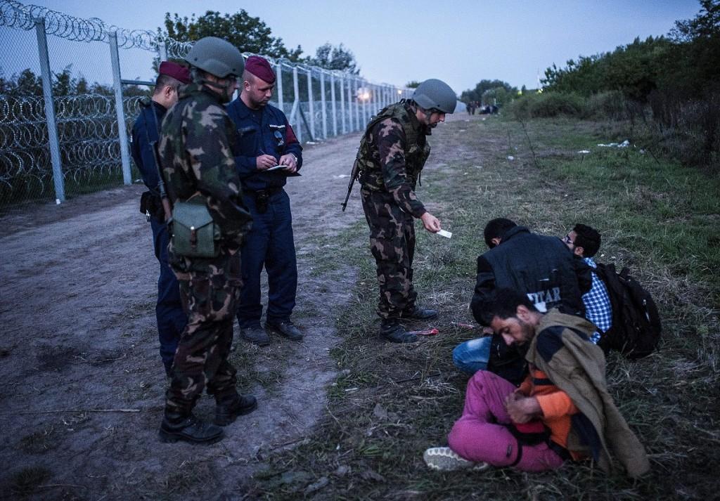Röszke, 2015. szeptember 15. Katonák és rendõrök három elfogott illegális bevándorlót õriznek a biztonsági határzár mellett a szerb-magyar határon, Röszke térségében 2015. szeptember 15-én. Szeptember 15-én hatályba léptek a migrációs helyzet miatti új szabályozások. MTI Fotó: Ujvári Sándor